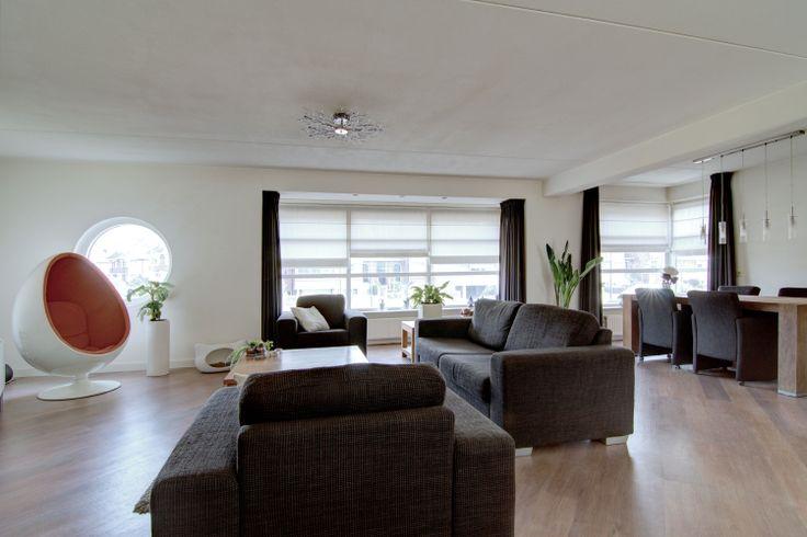 Aan de linkerzijde kijkt u naar de tuindeuren van de lager gelegen woonkeuken en aan de rechterzijde ziet u de extra brede voorzijde van de woonkamer met het ronde raam, de opvallend brede erker en het speelse hoekraam. Ook hier valt het op dat u vanuit een iets hoger punt naar buiten kijkt. Met een afmeting van circa 50m² is deze woonkamer opvallend ruim.  www.theo-keijzers.nl