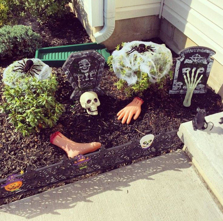 dollar tree halloween decor to turn your flower bed into a spooky grave yard