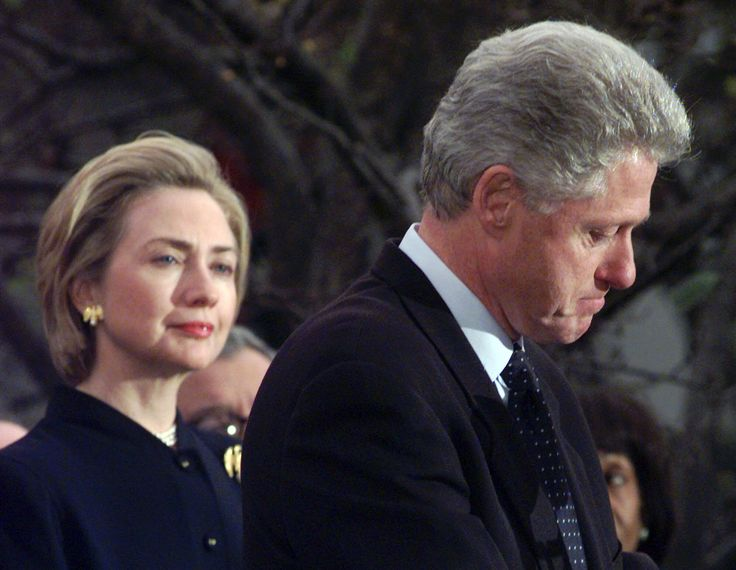 Hillary Clinton watches President Bill Clinton as he thanks Democratic members of the House of Representatives on Dec. 19, 1998. (Susan Walsh / The Associated Press)