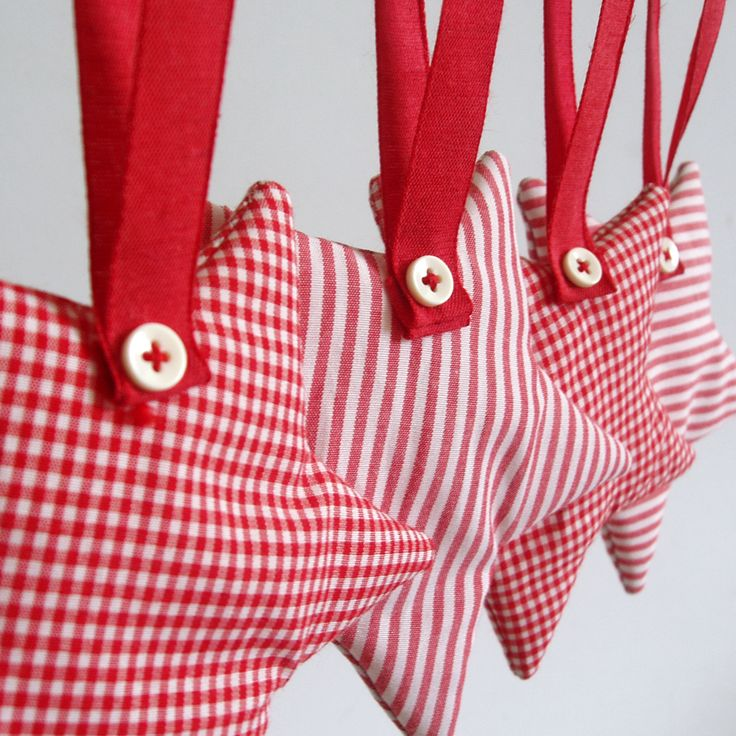 Fabric, hanging star ornaments in 2 variations, plaid red and stripy red.