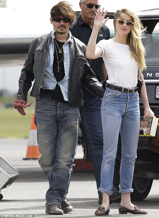 Affectionate: The 51-year-old star placed a hand gently on his wife's back as she waved to fans who saw them arriving at Brisbane airport