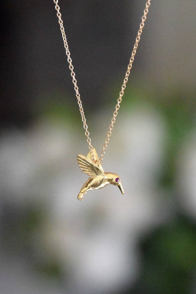 A gorgeous hummingbird charm on a delicate chain. Featuring genuine rubies set into the hummingbird's eyes. BENEFITTING KIND CAMPAIGN: 20% of the retail price of this necklace will go to benefit Kind