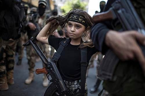 20 Breathtaking Pictures Of The Human Race: Equipped with an actual Kalashnikov rifle, this young Palestinian girl rallies with  Islamic Jihad militants in Gaza City
