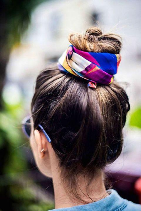 Elige un pañuelo corto y colorido para decorar tu moño alto. Es una manera de añadir accesorios y estilo a uno de los peinados más habituales para evitar el calor en verano. Lo hemos visto en Pinterest.