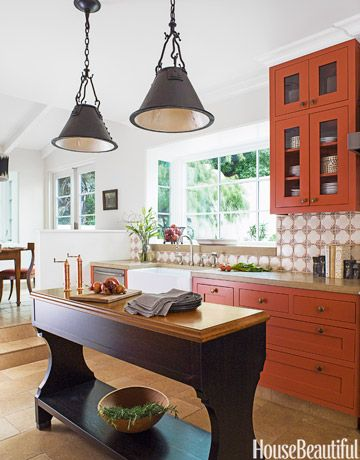 A liberal dose of spicy orange is the detail that makes this California kitchen designed by Melanie Coddington really special.The hand-forged iron Chauvin lanterns from Dessin Fournir were painted white inside to reflect more light onto the island. Shaws Original fireclay apron sink from Rohl. Faucet from Rocky Mountain Hardware. Bosch dishwasher. Benjamin Moore Aura in Salsa Dancing on cabinets and Oatmeal on walls.