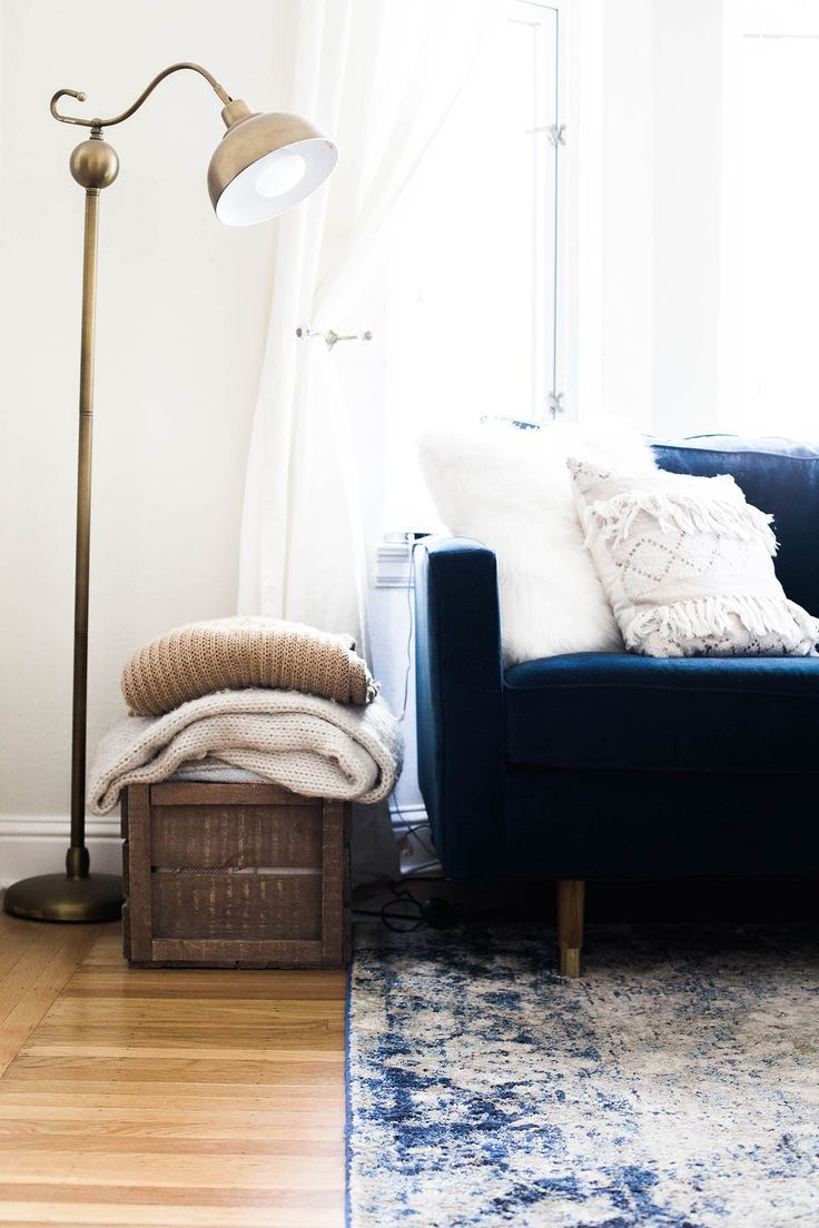 Dark blue couch, blue and white printed boho rug, brass gold lamp and woven basket