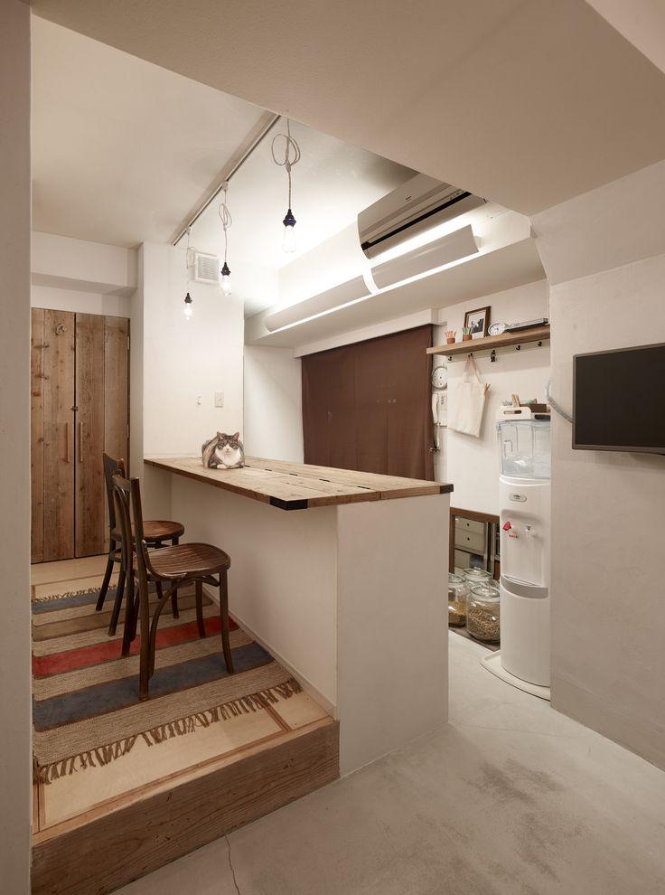 足場板再利用と収納アイデアでお気に入りのワンルームマンションにリノベーション。キッチンの床はモルタルで土間風に仕上げています。壁は、調湿・消臭性のあるシラス壁、カウンターや収納扉には、建築現場で使われた足場板のリユース材を用いて素材にもこだわりました。錆や釘痕などもラフな仕上がりにはチャームポイントになります。キッチンは奥行きがコンパクトな業務用のステンレスキッチンをセレクトしました。造作カウンターを閉じればお客様のおもてなしの場として、また、愛猫たちの水廻りでのいたずらも防ぎます。人も猫も、互いの気配を感じながら心地よく過ごせる空間が完成しました。