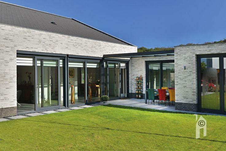 Glazen puien en aluminium kozijnen. Drie opengaande tuindeur-combinaties en overdekt terras tussen slaapkamer en keuken.