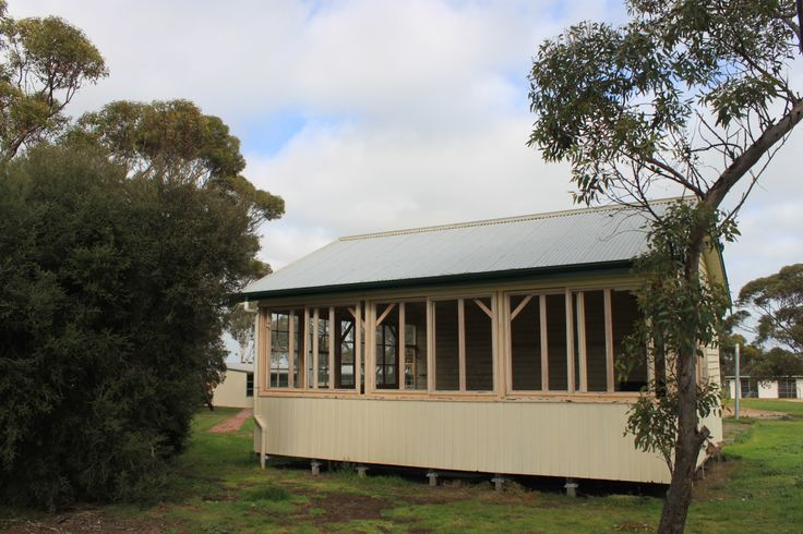 The Natimuk Pavilion Classroom constructed by the Victorian Public Works Department in 1914 as an open air classroom. The rectangular timber structure with a gabled roof, accommodated 48 children in dual seater desks. 3 sides of the classroom are boarded with weatherboards to the height of 3'; above that, adjustable canvas shutters were fitted to the roofline. The back wall where the blackboard was mounted was boarded from floor to ceiling. The room was built on sleeper plates for easy…