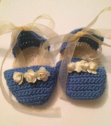 Patucos para bebé de ganchillo. Sandalias para niña tejidas a mano en crochet en hilo azul con detalle de flores en beige y lazo de organza en el mismo tono.  www.lafabricadecucadas.com