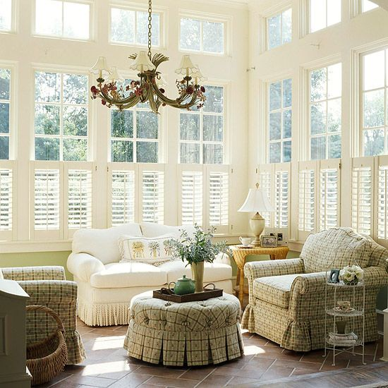 Wood shutters -- installed on the lower portions of the tall windows -- add light-filtering privacy in the sunroom. This type of window treatment creates a sense of intimacy by visually reducing the room's volume without sacrificing the views that connect the sunroom to the surrounding landscape.