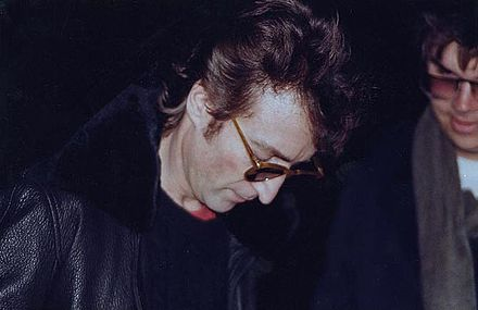 Lennon (left) signing a copy of Double Fantasy for Chapman several hours before the murder