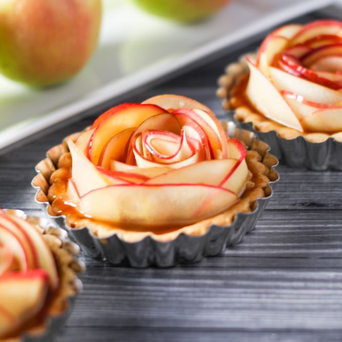 These Salted Caramel Apple Tartlets are not only amazingly delicious, but beautiful too! Thin apple slices are arranged to look like a rose and drizzled with a yummy, spiked salted caramel sauce. Perfect for Valentine's Day or holiday dinners.   platingsandpairings.com