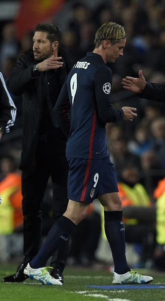 Atletico Madrid's forward Fernando Torres (R) passes by Atletico Madrid's Argentinian coach Diego Simeone as he leaves the pitch after being sent off by referee during the UEFA Champions League quarter finals first leg football match FC Barcelona vs Atletico de Madrid at the Camp Nou stadium in Barcelona on April 5, 2016.