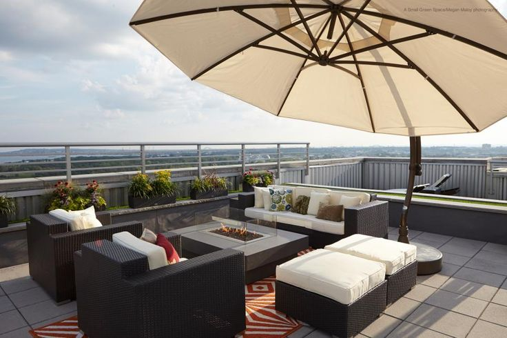 Contemporary outdoor furniture surrounds a modern fire pit underneath a large patio umbrella on this New York rooftop deck.