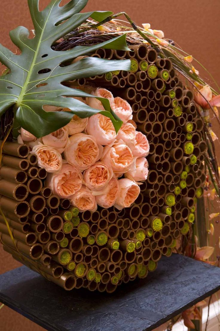 """A """"vase"""" made of a variety of painted tubes makes for an arresting receptacle for this swirling arrangement"""