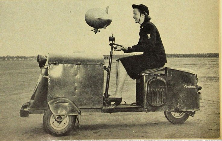 """On July 30, 1942, the US War Department established the US Navy Waves, the name was the acronym for """"Women Accepted for Volunteer Emergency Service."""" This photograph was taken at the South Weymouth Naval Air station in Weymouth, Massachusetts and shows a Wave working as a dispatch rider taking messages between hangers. Note: she riding on a Cushman ~"""