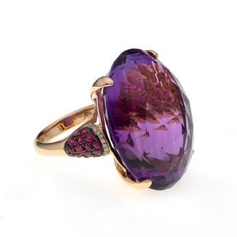 A statement amethyst and ruby dress ring. A fantastic oval cut amethyst of 51.90cts, beautifully faceted to show its true depth of colour, beset with ruby and diamond shoulders, all mounted in a warm 18ct rose gold setting