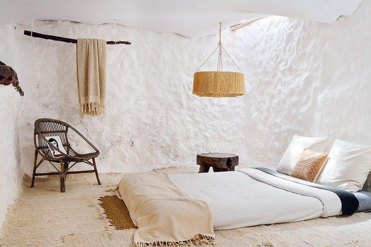 A dormir - AD España, © Belén imaz En uno de los dormitorios, con los muros originales de piedra de la vivienda, alfombras y mantas de lana marroquíes, silla de ratán años 60, taburete de madera vintage y lámpara con pantalla recubierta de rafia, diseño de David Swayne.
