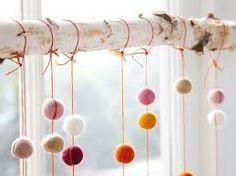 Scandinavische kerst. Een houten stok, maar met een ander doel! Leuke gekleurde ballen van stof met touwtjes asymmetrisch aan elkaar verbonden.