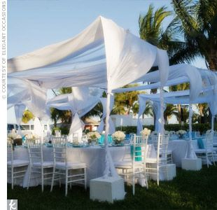 Gauzy canopies added a chic touch to these reception tables without overwhelming the outdoor environment.
