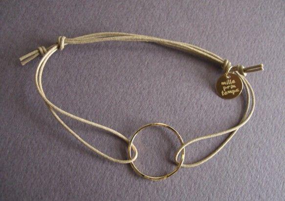 ゴールド色のリングとベージュのコードのブレスレットです。白シャツに合いますよ!紐の両端を引っ張って長さ調節できます。コード コットン100%ブランドタグ ゴールド色