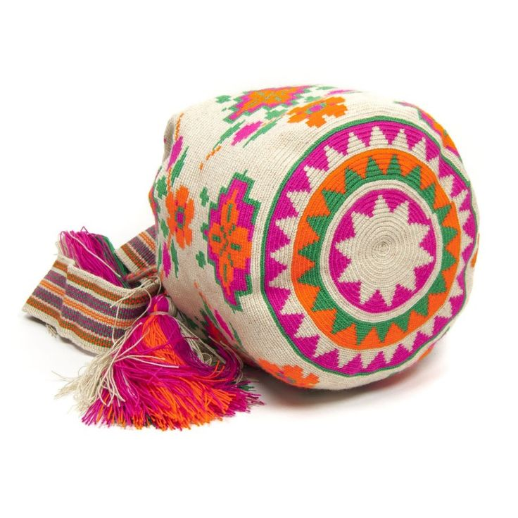 Colores: Tejido a mano en Crochet. Asa tipo banda. Bolso Wayuu en color Beige con tonos en naranja, rosa y verde. Medidas aproximadas: - Alto: 25 cm - Cinta: 106 cm - Diámetro: 25 cm Cada bolso está hecho a mano, por tanto es una pieza única. El diseño puede variar ligeramente.