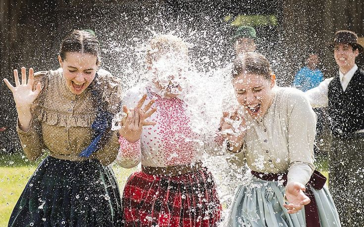 Women in traditional costumes are sprayed with water by men as members of the Marghareta Dance Group perform Easter folk traditions in the Museum Village in Nyiregyhaza, Hungary. According to tradition, young men pour water on young women who in exchange present their sprinklers with beautifully coloured eggs on Easter Monday.
