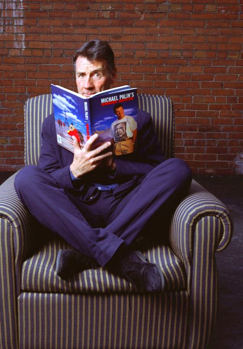 Michael Palin reading his own book while wearing a purple suit while sitting on a striped couch