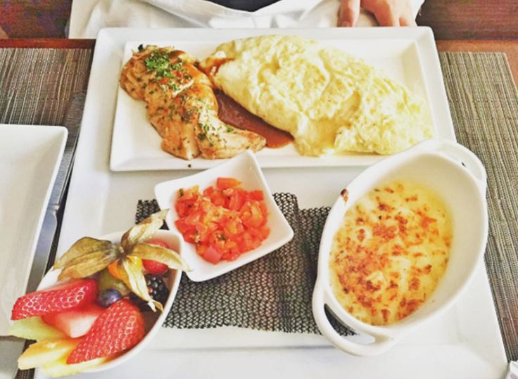 A meal of omelette, veggies, and fruit sits on a table at brunch spot Wildflower Grill in Edmonton.