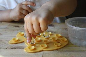 Montessori - Marbles on a bath mat