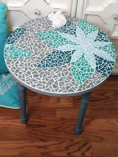 Learn how to make a mosaic table with an artistic design, including how to transfer the design, how to cut tiles to fit, and how to mix and apply grout.