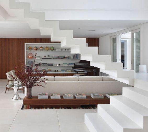Localizada bem no meio da sala, essa escada é moldada em concreto, formando um volume contínuo. O acabamento todo branco parece cimento com pó de mármore ou pintura, já que não tem emendas.