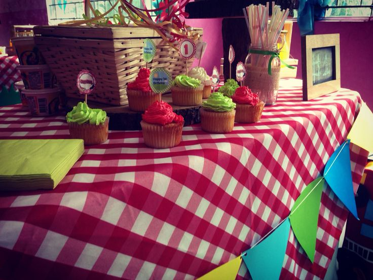 Mantel de cuadros con banderín en la mesa , Cupcakes y cesta de picnic