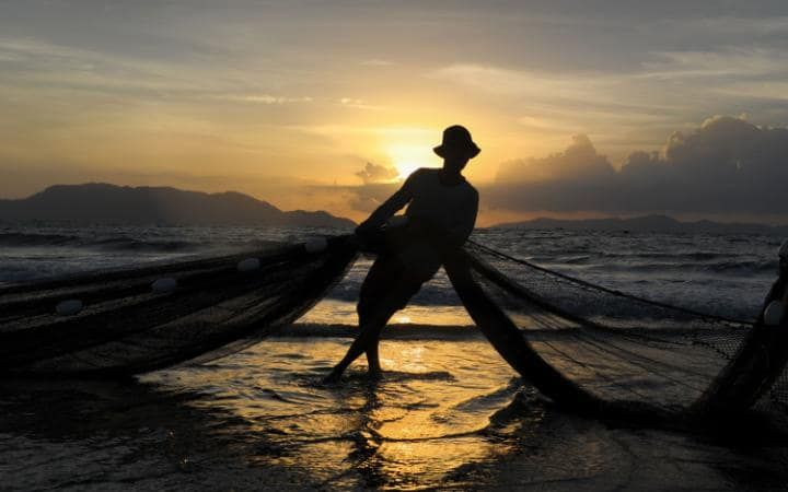 A fisherman pulls his net up the beach in Banda Aceh after a night of fishing
