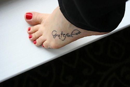 """Pequeño tatuaje en el pie que dice """"Grateful"""", que significa """"Agradecido""""."""