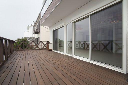 「海を望む海岸沿いの家」 横須賀市のI様邸外観玄関前の縦格子、深い軒の出、木目の外壁がすこし和風でモダンな外装としました。外観は海を向いたデザインを意識しました。広いウッドデッキ、大きな開口部、船のような丸窓、シンプルなガラスのバルコニー手摺、深い軒と海を向いた斜めの袖壁。きれいな白い外壁とデッキの木の色がよく合う海を望む家です。LDK