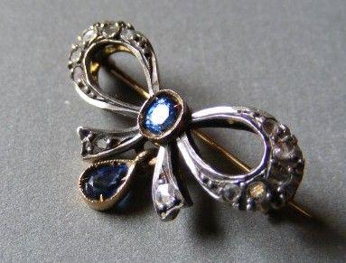 Nádherná brož je vyrobena ze zlata ryzosti 750/1000 - spodní část šperku a upínací jehla. Vrchní část stříbro 925/1000. Osázeno nádhernými přírodními diamanty a safíry. Diamanty mají routový, růžicový brus. Váha 3 g.  Rozměr brože cca 2,4 x 1,5 cm. Staré i nové puncovní značení, součástí boleta PÚ. Výborný stav, první pol. 20. století.