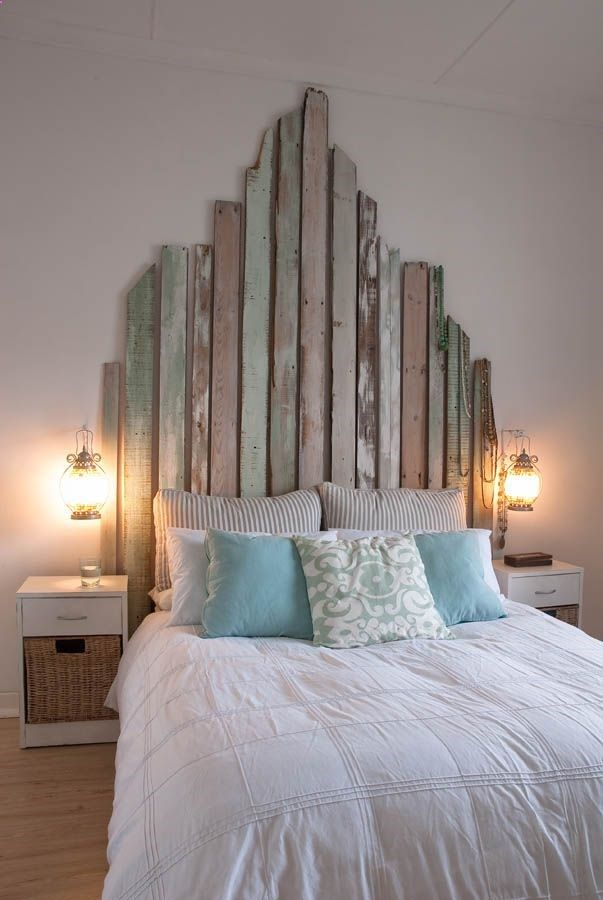 Reclaimed boards in soft, worn pastel colours are repurposed as an interesting headboard in this principle bedroom.
