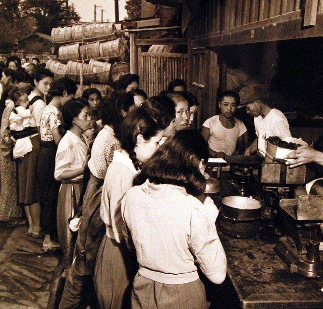 「食料を求めて」Japanese people readjusting themselves to life in Tokyo, Japan, after the end of the war. Food distribution center. Photograph received 17 September 1945.