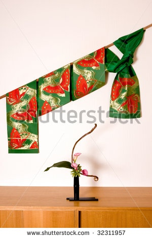 stock photo : Ikebana flower arrangement and obi (part of kimono dress) in a Japanese interior