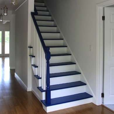Painted Staircase - Accenting a white staircase with a dark paint color is as decorative as it is functional, because a dark color tends to mask scuff marks.