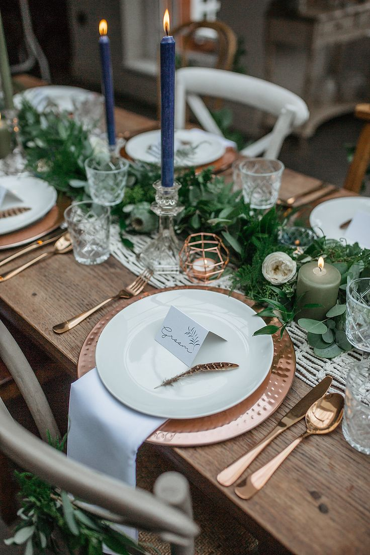 Bohemian macrame wedding table runner with copper cutlery, copper metal charger plate, white napkins and lush textured foliage garland with succulents, poppy seed heads and white David Austin roses. Tall navy blue and green dinner candles in cut glass candlesticks.