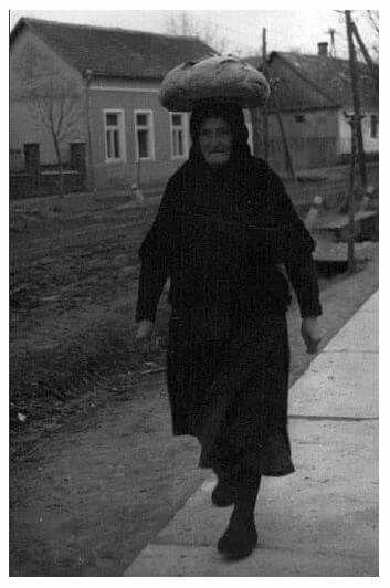 """Tekercs segítségével, a fején viszi haza a pékségből a kenyerét egy asszony 1962-ben Karádon (Somogy m.) A kenyértésztát még sokan maguk gyúrták otthon abban az időben, reggel elvitték a pékhez, délre kisült a """"saját"""" kenyér. Fotó: Horváth Terézia"""
