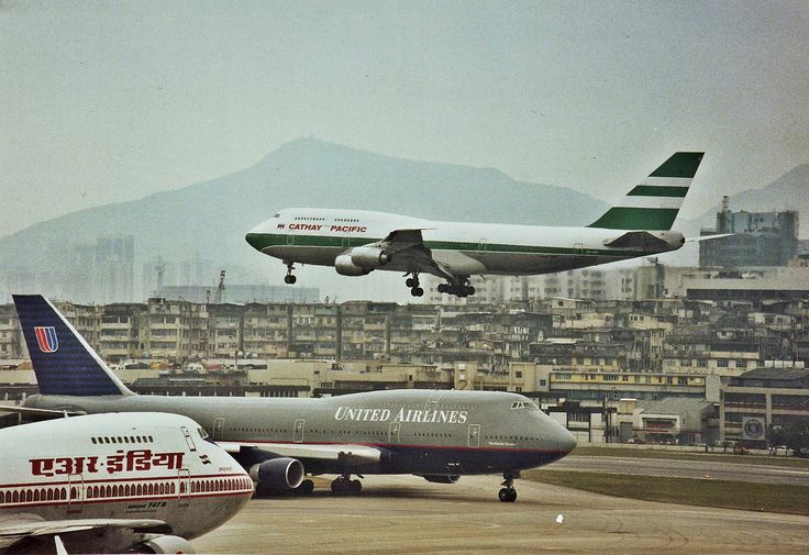 Hong Kong-Kai Tak International Airport with 3 generations of the Boeing 747 present: Air India Boeing 747-237B, United Airlines Boeing 747-422, and Cathay Pacific Boeing 747-367