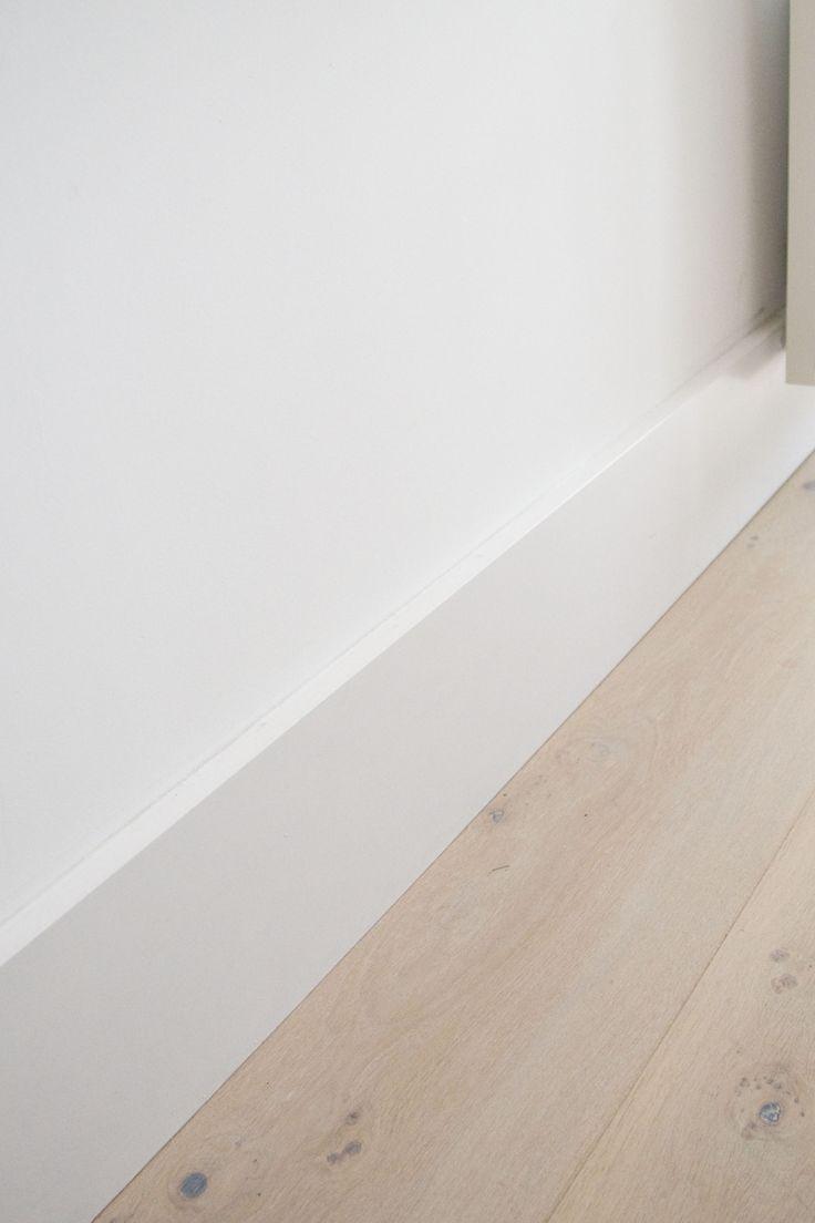 Eiken houten vloer mooi afgewerkt met een hoge witte plint. www.pieterdeboer.com