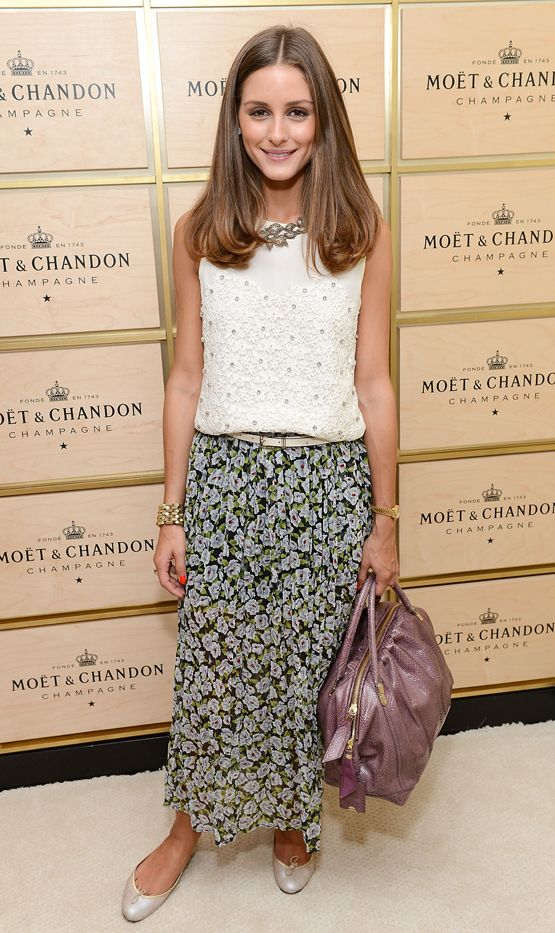 Olivia Palermo pairs a flowy floral skirt with a white top, purple bag, white skinny belt, and white ballet flats