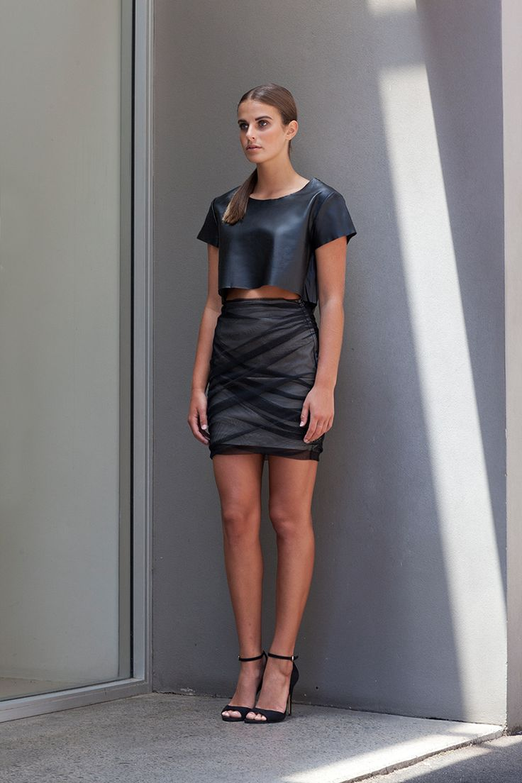 The Fracture Ruched Mesh Skirt is a fitted silhouette that features black mesh ruching over a chic beige base.