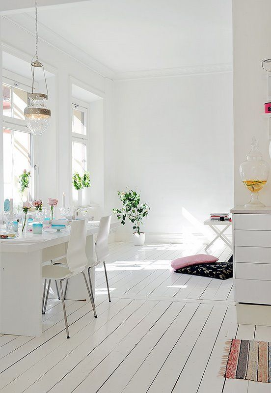 The white floors and pops of color give this minimalist space so much charm.
