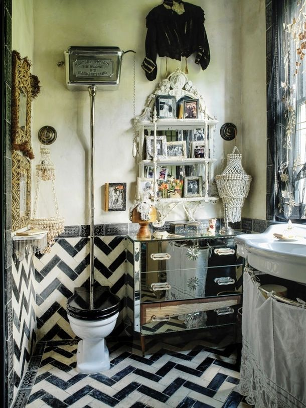 Gorgeous vintage tiles, in a chevron pattern, make the bathroom: a mirrored dresser adds a bit of storage and a bit of glam.